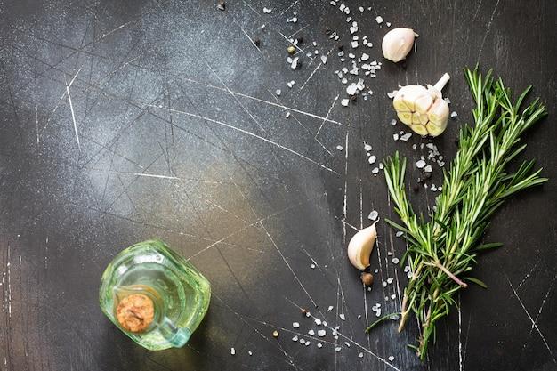 Kruiden olijfolie en kruiden op een donkere stenen of leisteen tafel ingrediënten voor het koken
