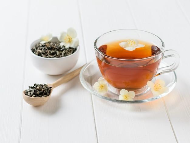 Kruiden thee, honing, jasmijn bloemen en een houten lepel op een houten witte rustieke tafel. de samenstelling van het ontbijt.