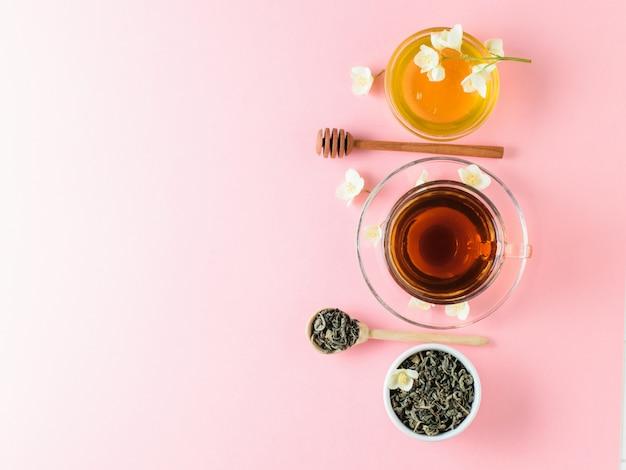Kruiden thee, honing, jasmijn bloemen en een houten lepel op een roze tafel. de samenstelling van het ontbijt. plat liggen.