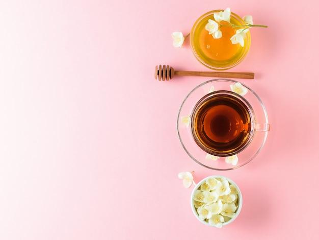 Kruiden thee, honing, jasmijn bloemen en een houten lepel op een roze tafel. plat liggen.