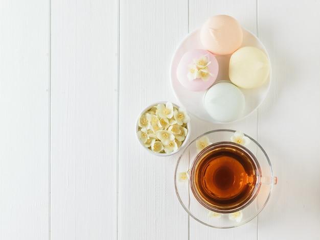 Kruiden thee, marshmallows en jasmijn bloemen op een tafel. de samenstelling van het ontbijt. plat liggen.