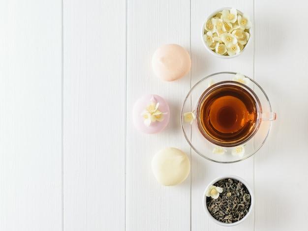 Kruiden thee, marshmallows en jasmijn bloemen op een witte houten tafel. de samenstelling van het ontbijt. plat liggen.