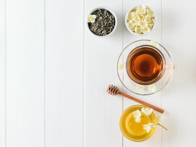 Kruiden thee met jasmijn en een kom van bloemen en honing op een tafel. de samenstelling van het ontbijt. plat liggen.