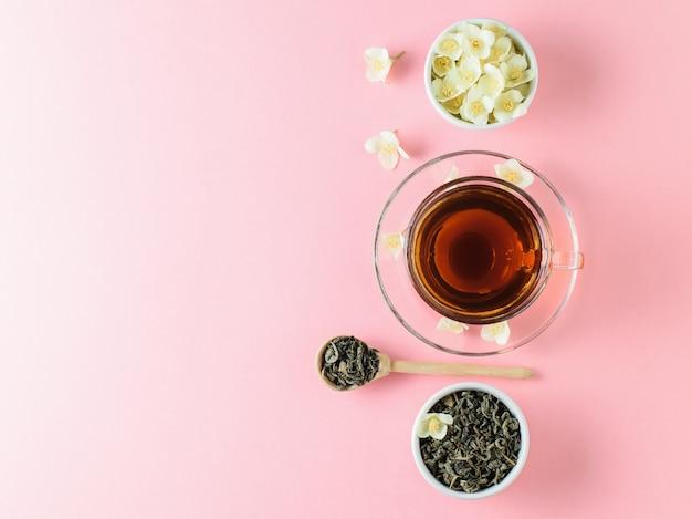 Kruiden thee met jasmijn en een kom van bloemen op een roze tafel. de samenstelling van het ontbijt. plat liggen.
