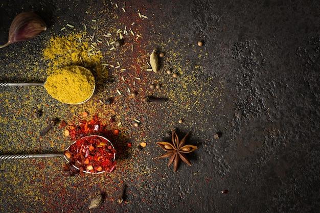 Kruiden voedsel achtergrond. selectie variëteit droog hele en gemalen kruiden op een zwarte achtergrond.