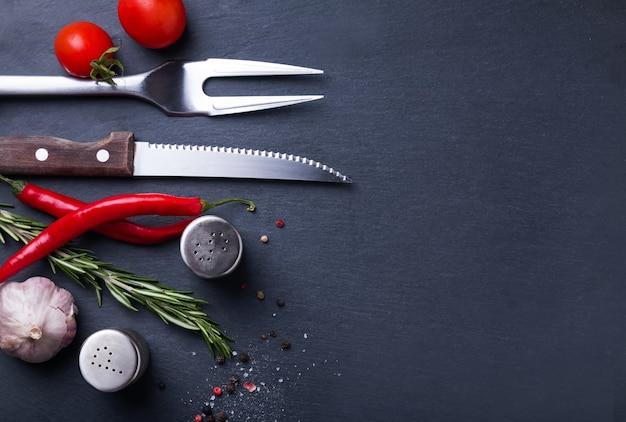 Kruiden voor biefstuk, vork en mes op de zwarte achtergrond bovenaanzicht