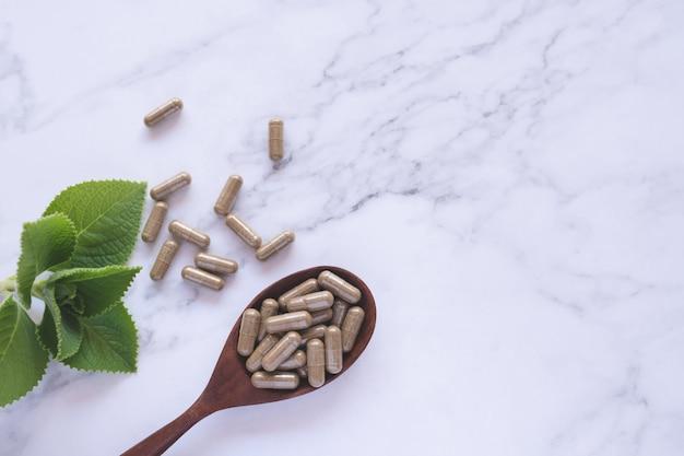 Kruidengeneeskunde in capsules op houten lepel met natuurlijk groen blad op wit marmer