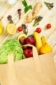 Kruidenier concept. volle papieren zak met verschillende soorten fruit.