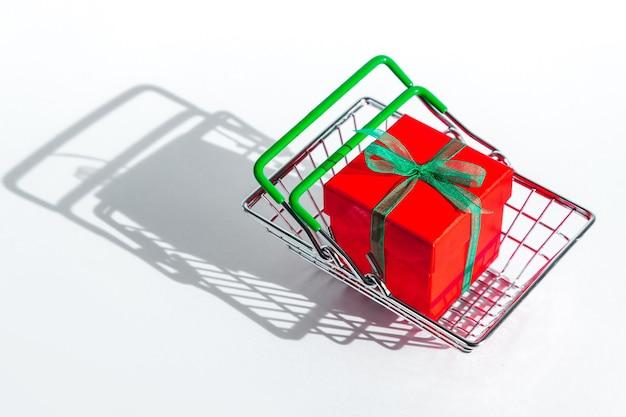 Kruidenierswinkel mand met rode geschenkdoos op wit