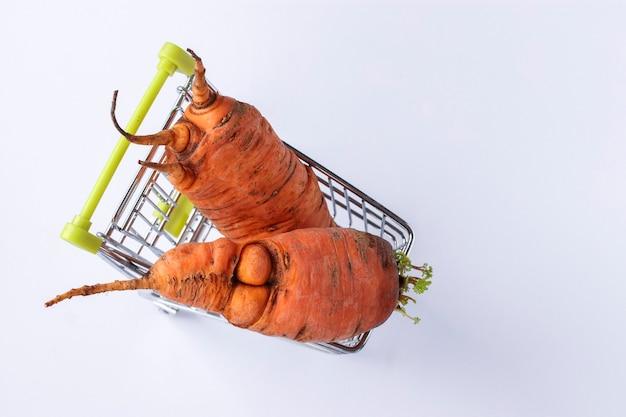Kruidenierswinkelkarretje met lelijke wortel op witte achtergrond. concept milieuvriendelijk winkelen, biologisch voedsel, bovenaanzicht