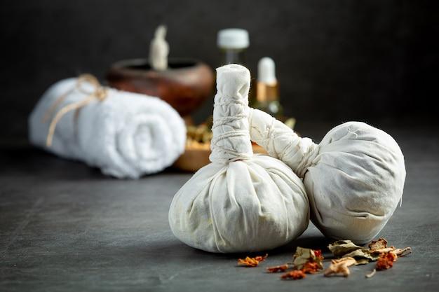 Kruidenkompres en apparatuur voor kruidenkuurbehandeling op een donkere vloer