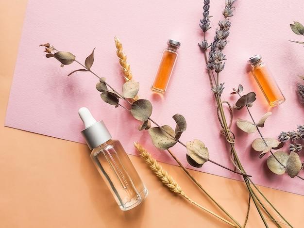 Kruidenolie en lavendelbloemen op pastelkleurmuur. fles etherische olie met lavendel. natuurlijke cosmetica met lavendel en sinaasappel, citroen voor zelfgemaakte spa