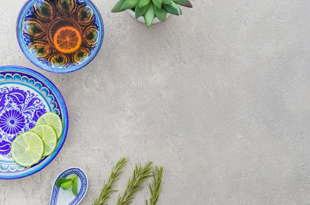 Kruidenthee gemaakt met rozemarijn; plakjes citroen; muntblaadjes op grijze gestructureerde achtergrond