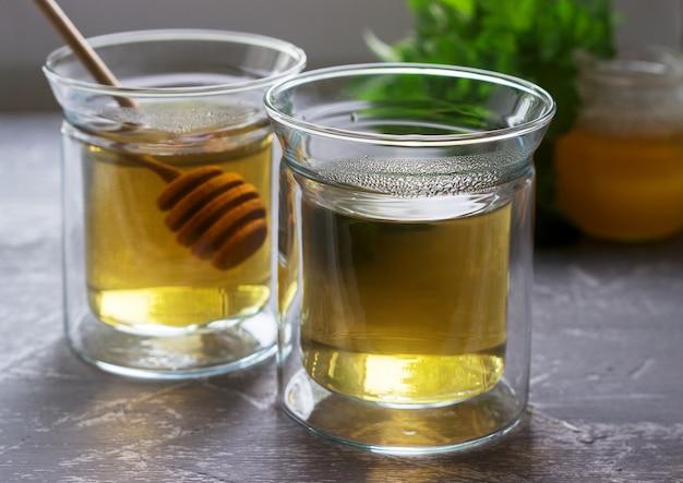 Kruidenthee gemaakt van munt en citroenmelisse met honing in glazen bekers. rustieke stijl.