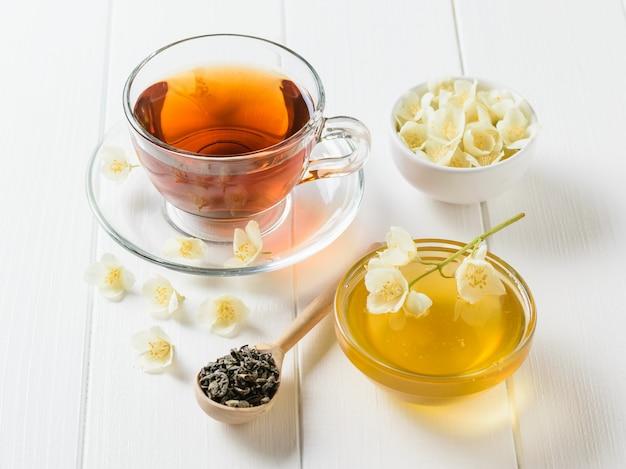 Kruidenthee, honing, jasmijn bloemen en een houten lepel op een rustieke witte tafel.