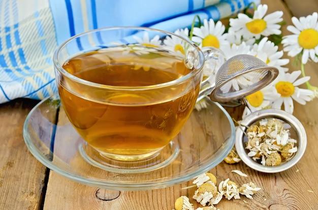 Kruidenthee in een glazen beker, een metalen zeef met gedroogde kamillebloemen, verse bloemenmadeliefjes, servet tegen een houten plank