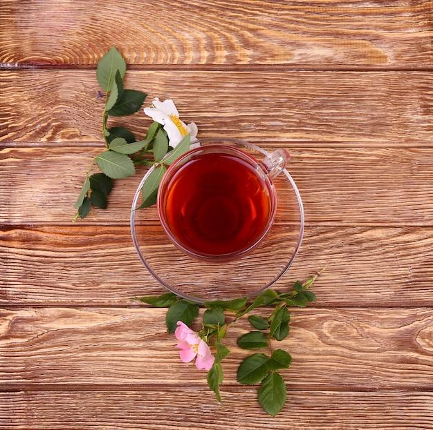 Kruidenthee in een glazen beker, verse bloemen op een achtergrond van houten planken