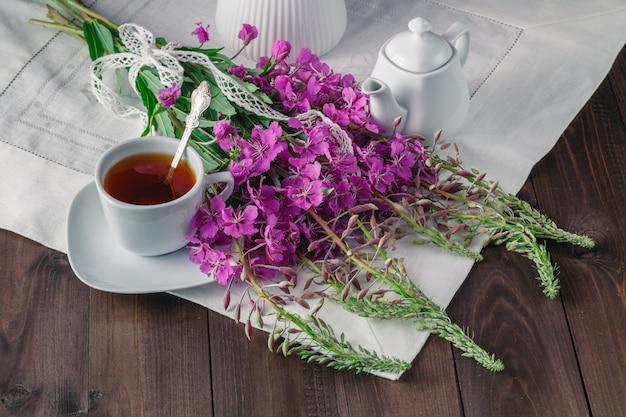Kruidenthee in een glazen beker, verse bloemen wilgeroosje tegen de donkere houten plank