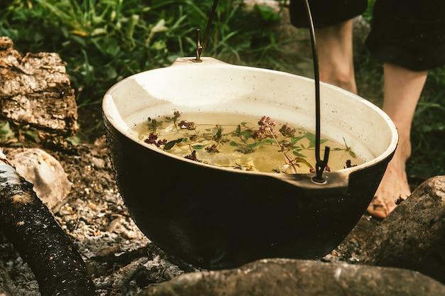 Kruidenthee in ketel wordt opgewarmd op vreugdevuur, omringd door stenen op de achtergrond van as in de buurt van groen gras en blote voeten. koken in de open lucht. actieve openluchtrecreatie. dicht in het wild kamperen.