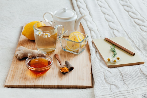 Kruidenthee met kamillebloemen, kurkuma en honing op een houten bord. behandeling van warme drank gember. folk remedies in bed. vrije tijd boek.
