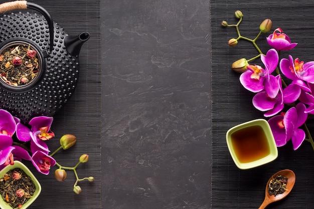Kruidenthee met zijn gedroogde ingrediënt en orchideebloem op zwarte placemat