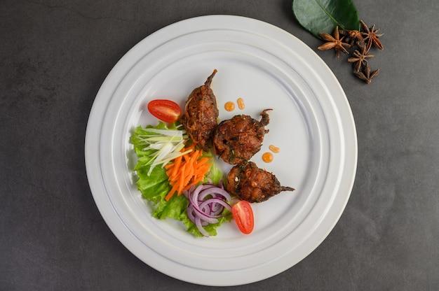 Kruidig fried stir catfish op witte plaat, thais voedsel.