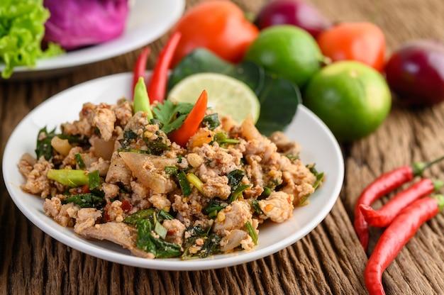 Kruidige fijngehakte salade op een witte plaat op houten tafel.
