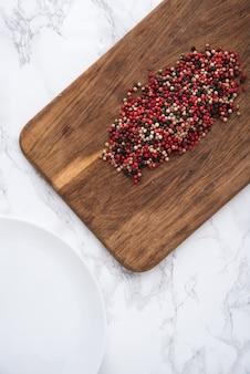 Kruidige gemengde peperbollenhoop op een houten scherpe raad