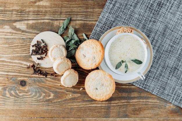 Kruidige melk in een kopje met munt, koekjes, kruidnagel bovenaanzicht op houten tafel