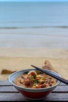 Kruidige soep van de riviergarnaal of tom yum kung in kom op houten lijst op strand dichtbij overzees