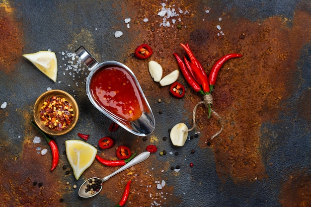 Kruidige tomatensaus en ingrediënten op zwarte achtergrond