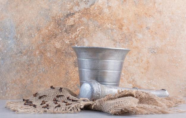 Kruidnagels in een zilveren vijzel en stamper om te mengen.