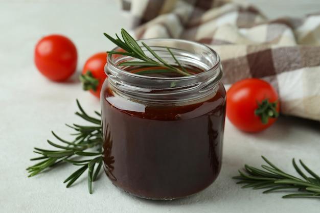 Kruik barbecuesaus, rozemarijn, tomaten en keukendoek op witte geweven lijst