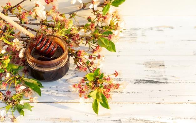 Kruik chocoladehoning met de lentebloemen op witte houten achtergrond