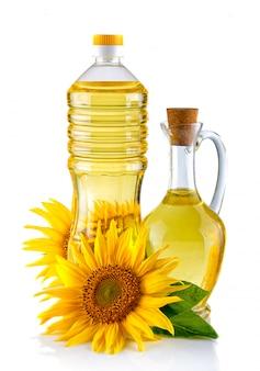 Kruik en fles zonnebloemolie met bloem op wit wordt geïsoleerd dat