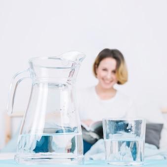 Kruik en glas die dichtbij vrouw lezen