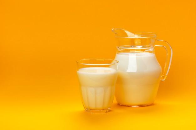 Kruik en glas melk op gele achtergrond met exemplaarruimte wordt geïsoleerd voor tekst, zuivelproductconcept dat