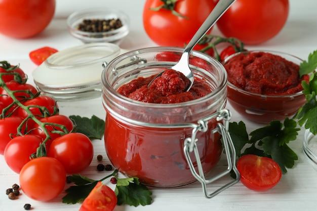 Kruik en lepel met tomatenpuree op witte houten lijst met ingrediënten