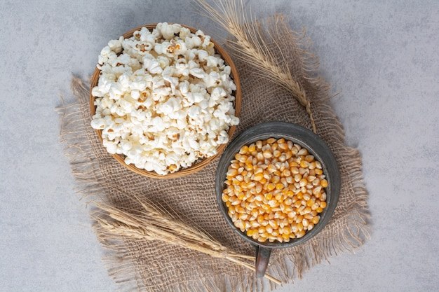Kruik gevuld met mais en kom gevuld met popcorn naast stengels tarwe op een stuk stof op marmer.