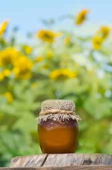 Kruik honing en zonnebloemen op houten lijst over bokeh-tuin. gezond eten concept