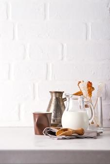 Kruik melk en gemalen koffie voor het maken van een drankje thuis op een stenen aanrecht tegen een witte keukenmuur