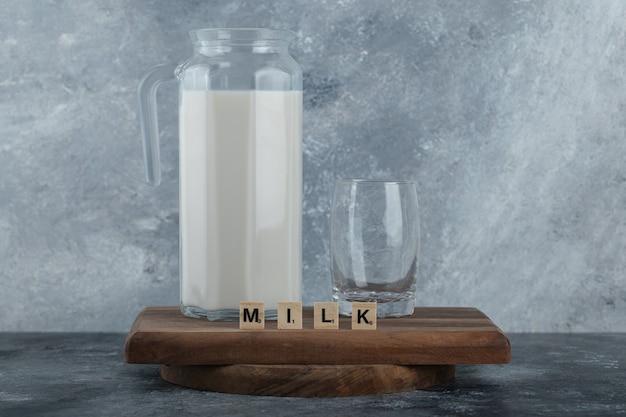 Kruik melk en glas water op een houten bord.