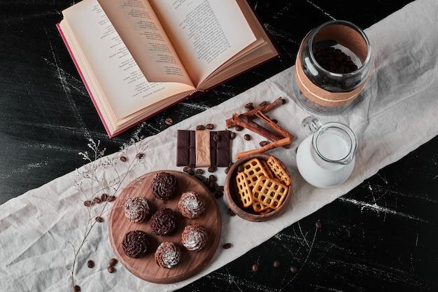 Kruik melk met koffiebonen en chocoladepralines.