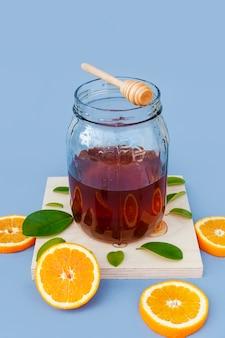Kruik met eigengemaakte honing en sinaasappelen