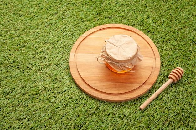 Kruik met eigengemaakte honing op een houten raad