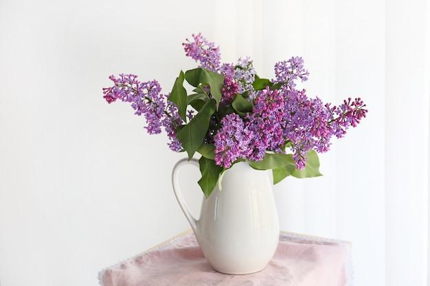 Kruik met mooie lila bloemen binnenshuis