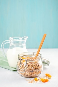 Kruik met zelfgemaakte muesli of havermoutmuesli met noten en gedroogde vruchten en melk.