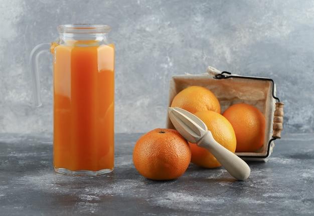 Kruik sap en mand met sinaasappelen op marmeren tafel.
