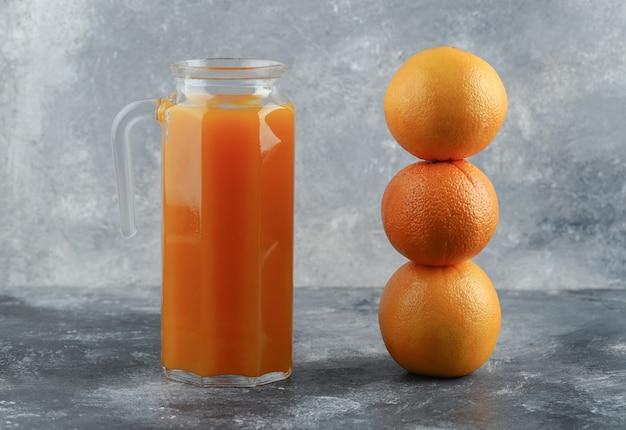 Kruik sap en sinaasappelen op marmeren tafel.