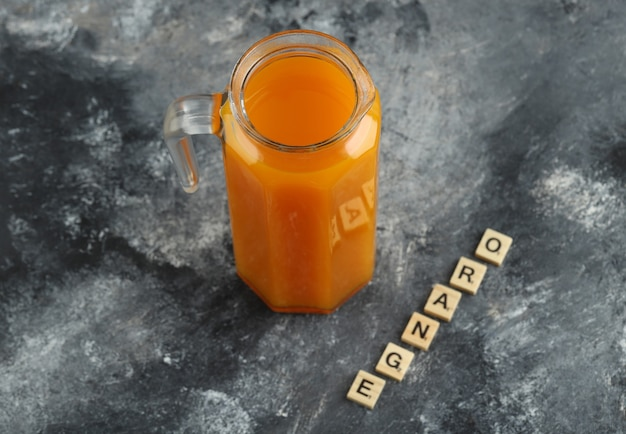 Kruik sinaasappelsap met houten letters op marmeren tafel.